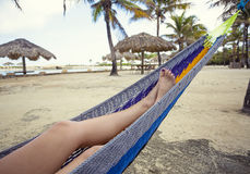 Beautiful female feet and legs relaxing in a hammock on the beach Stock Photo