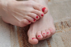 Beautiful female feet with pedicure. On beige carpet Royalty Free Stock Image