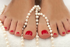 Beautiful female feet with red pedicure  on white and decorated with pearls Stock Photo