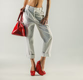 Beautiful female feet in red shoes and bag. Female feet in red shoes and bag Stock Photos