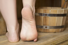 Beautiful female feet in sauna, bath accessories Royalty Free Stock Photography