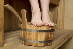 Beautiful female feet in sauna, bath accessories Stock Images