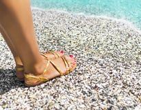 Beautiful female feet on sea sand Stock Photography