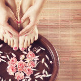 Beautiful female feet in spa composition. Beautiful legs, flowers, petals and ceramic bowl. Summer spa background Royalty Free Stock Images