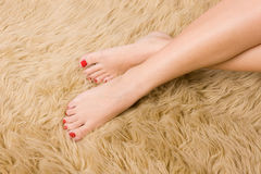 Beautiful  female feet on wool carpet Royalty Free Stock Images