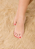 Beautiful  female feet on wool carpet Stock Photo