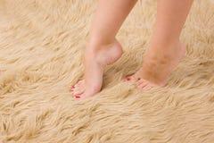 Beautiful female feet on wool carpet royalty free stock photography