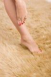 Beautiful  female feet on wool carpet Stock Image