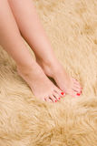 Beautiful  female feet on wool carpet Royalty Free Stock Photos