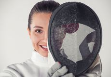 Beautiful female fencer. In protective clothing is holding a mask, looking at camera and smiling, on gray background Royalty Free Stock Photo