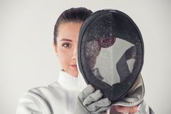 Beautiful female fencer. In protective clothing is holding a mask and looking at camera, on gray background Stock Image