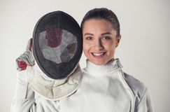 Beautiful female fencer. In protective clothing is holding a mask, looking at camera and smiling, on gray background Royalty Free Stock Photography
