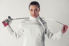 Beautiful female fencer. In protective clothing is holding a weapon and looking at camera, on gray background Royalty Free Stock Photo
