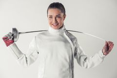 Beautiful female fencer. In protective clothing is holding a weapon and smiling, on gray background Stock Images