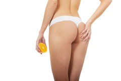 Beautiful female figure with an orange. Stock Image