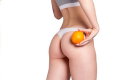 Beautiful female figure with an orange holds near the ass Royalty Free Stock Images