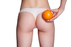 Beautiful female figure with an orange holds near the ass Stock Image