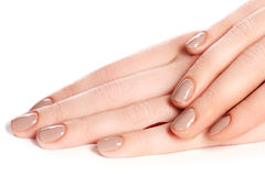 Beautiful female finger nails with beige nail closeup on petals. Royalty Free Stock Photography