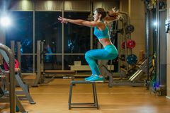 Beautiful female fitness athlete performs box jumps in a dark gym royalty free stock photography