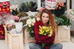 Beautiful female florist in flower shop. Beautiful business woman-the florist with long red hair,works at a flower shop on drafting of gift bouquets from fresh Royalty Free Stock Photography