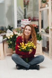 Beautiful female florist in flower shop. Beautiful business woman-the florist with long red hair,works at a flower shop on drafting of gift bouquets from fresh Stock Images