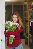 Beautiful female florist in flower shop. Beautiful business woman-the florist with long red hair,works at a flower shop on drafting of gift bouquets from fresh Stock Photography