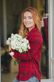 Beautiful female florist in flower shop. Beautiful business woman-the florist with long red hair,works at a flower shop on drafting of gift bouquets from fresh Royalty Free Stock Image