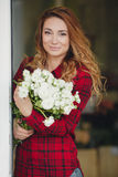 Beautiful female florist in flower shop. Beautiful business woman-the florist with long red hair,works at a flower shop on drafting of gift bouquets from fresh Stock Photo