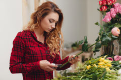Beautiful female florist in flower shop. Beautiful business woman-the florist with long red hair,works at a flower shop on drafting of gift bouquets from fresh Stock Image