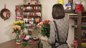 Beautiful female florist working indoor. Shot from behind of a lovely woman with short brunette hairs making a rose bouquet. She is holding a bunch of roses stock footage