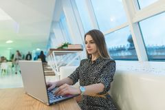 A beautiful female freelancer works for a laptop in a cafe with a stylish modern interior. royalty free stock photography
