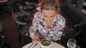 Beautiful female Frenchwoman in a variegated shirt eats a traditional French onion soup with croutons and greens in a. Restaurant. Slow Motion stock video footage