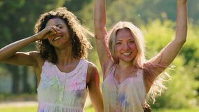 Beautiful female friends covered in colorful paint hugging, smiling to camera. Stock footage stock video