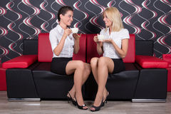 Beautiful female friends drinking coffee on the sofa Stock Photos