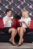 Beautiful female friends sitting with coffee cups on the sofa Royalty Free Stock Photos
