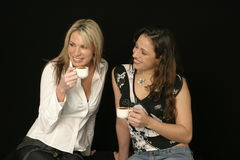 Beautiful female friends smiling. While having a cup of hot chocolate or coffee Stock Photography