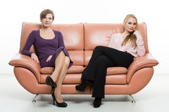Beautiful female friends on the sofa. two Royalty Free Stock Photography