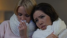 Beautiful female friends suffering from flu, sitting at home in big scarves. Stock footage stock video footage