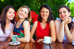 Beautiful female friends in summer cafe Stock Images