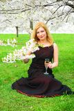 Beautiful female with glass of champagne in the sakura garden Stock Images