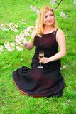 Beautiful female with glass of champagne in the sakura garden Royalty Free Stock Photography
