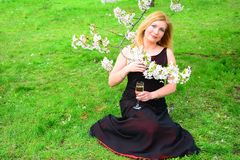 Beautiful female with glass of champagne in the sakura garden Stock Photo