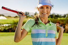 Beautiful female golfer holding golf club on field. Close up portrait of beautiful female golfer holding golf club on field. Young woman standing on golf course Royalty Free Stock Photos