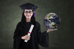 Beautiful female graduate holding earth in class Stock Photos