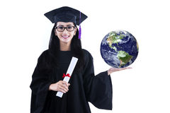 Beautiful female graduate holding earth - isolated. Beautiful female graduate holding 3D earth planet and certificate, isolated on white Royalty Free Stock Images