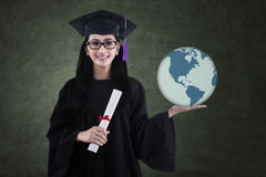Beautiful female graduate holding world globe in class Stock Images