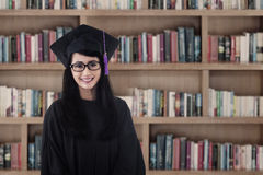 Beautiful female graduate smiling at library Stock Image