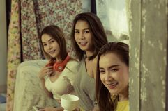 Beautiful female group three friends happily enjoy on sofa with fun in living room at home with bright smile morning,with warm. Sunshine, concept relaxation and stock image