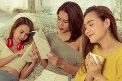 Beautiful female group three friends happily enjoy on sofa with fun in living room at home with bright smile morning,with warm. Sunshine, concept relaxation and stock images