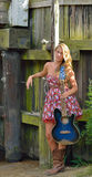 Beautiful female guitar player outdoors. Stunning and sexy young woman in strapless dress and cowboy boots outdoors playing a blue guitar - music series Royalty Free Stock Photography